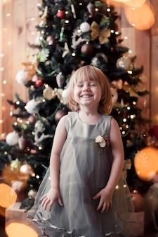 크리스마스 트리 infront 서 크리스마스를 기다리는 어린 소녀