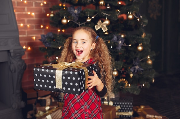 プレゼントとクリスマスツリーの近くに立っている少女