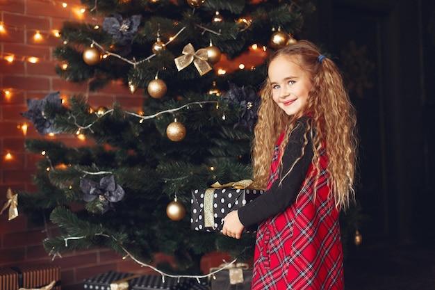 Маленькая девочка стоит возле елки с подарком