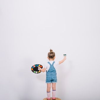 Little girl standing on chair and painting wall with brush