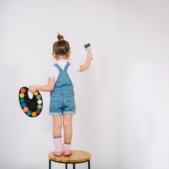 Little girl standing on chair and painting white wall with brush