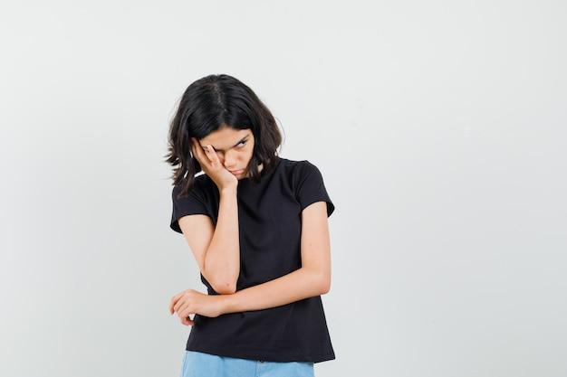 Bambina in piedi nel pensiero posa in maglietta nera, pantaloncini e guardando offeso, vista frontale.
