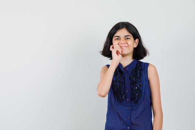 Bambina in piedi nella posa di pensiero e sorridente in camicetta blu