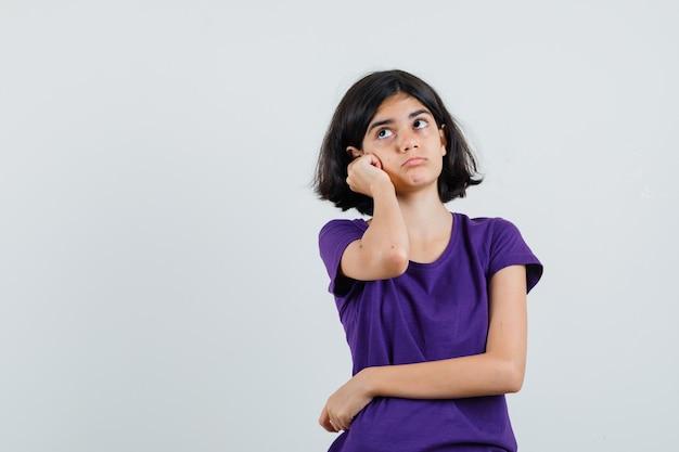 Bambina in piedi nella posa di pensiero in maglietta e guardando perplesso