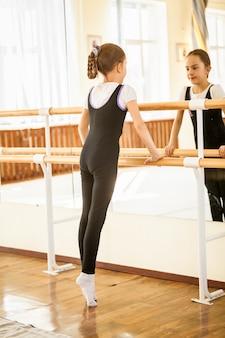 Little girl standing on tiptoe at dance class near mirror