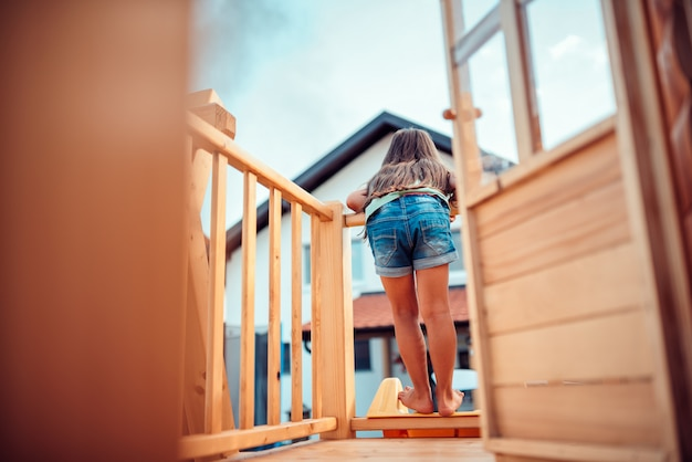 Little girl standing in treehouse with her back turned