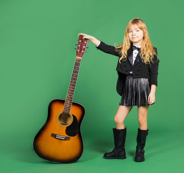 Little girl standing with acoustic guitar