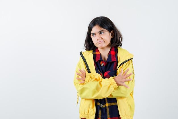 Маленькая девочка стоя со скрещенными руками в клетчатой рубашке, куртке и нерешительно глядя, вид спереди.