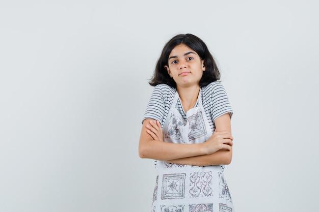 Маленькая девочка стоя со скрещенными руками в футболке, фартуке и выглядела смущенной.