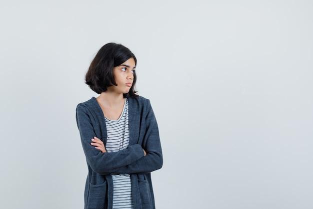 Tシャツ、ジャケット、躊躇しているように腕を組んで立っている少女