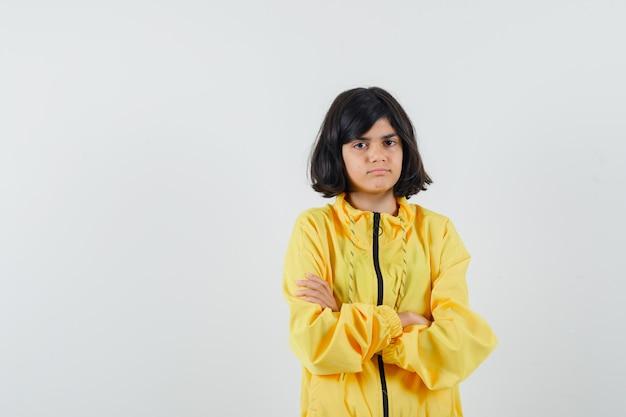Bambina in piedi con le braccia incrociate in felpa con cappuccio gialla e guardando pensieroso, vista frontale.
