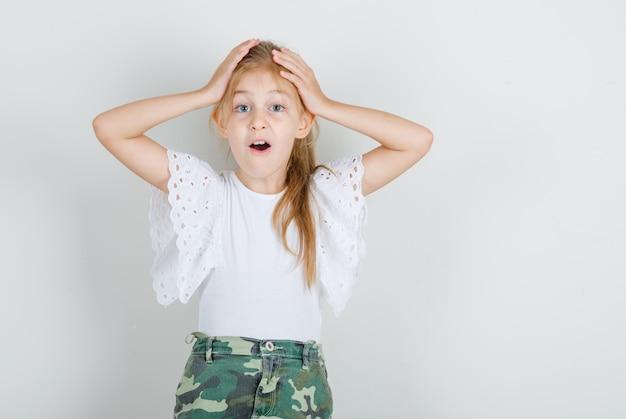 白いtシャツで頭の上の手で立っている女の子