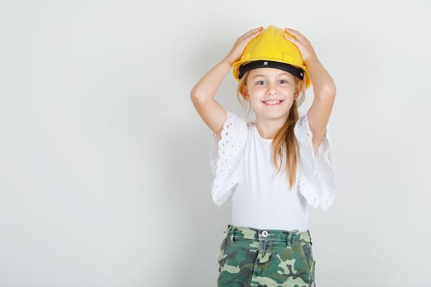 白いtシャツのヘルメットに手で立っている女の子
