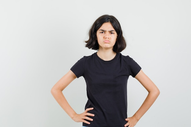 Маленькая девочка стояла с руками на талии в черной футболке и выглядела мрачно. передний план.