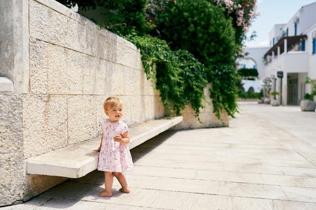 어린 소녀는 안뜰의 돌담 근처 벤치에 서 있다