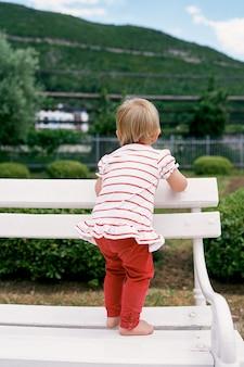어린 소녀는 녹색 공원 뒷모습에서 흰색 벤치에 맨발로 서 있다