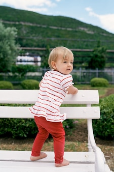 Little girl stands barefoot on a white bench in a green park