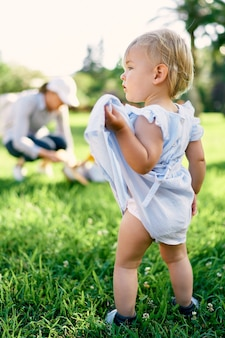 Little girl stands on a green lawn lifting the hem of her dress with her hand