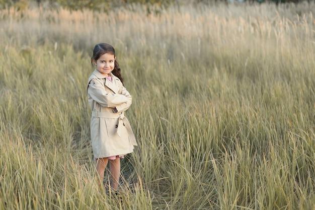 小さな女の子が畑に立っています。
