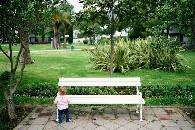 어린 소녀는 공원에서 화이트 벤치 근처 서