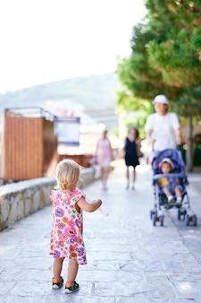 어린 소녀는 자갈길에 서서 아이들과 함께 걷는 사람들을 바라본다