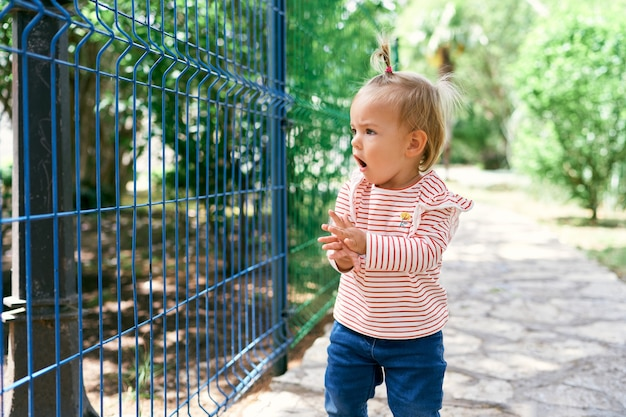 Little girl stands on a paved path near a metal fence with an open mouth