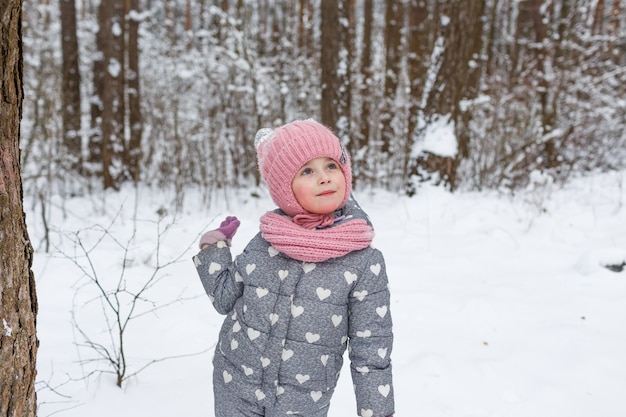 A little girl stands in a snow-covered forest and looks up. children's games in the winter forest. family winter vacation with a child.