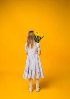 A little girl stands with her back to a bouquet of yellow tulips on yellow