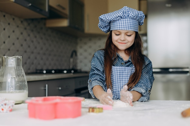 Little girl stir the dough attentively and with pleasure