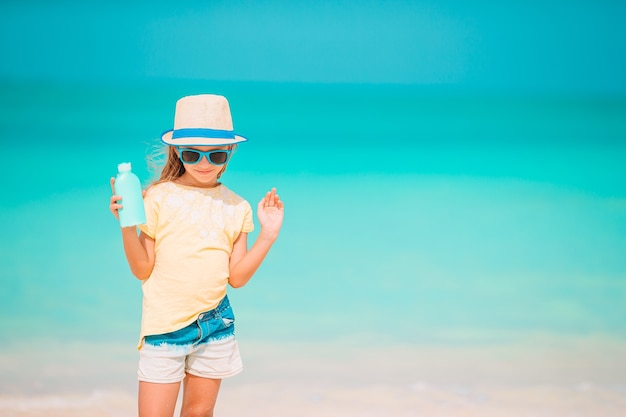 Little girl in straw hat on the beach with sun cream bottle. sun protection
