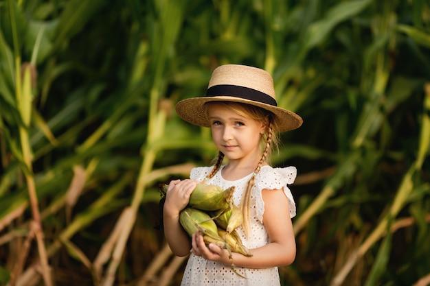 Little girl in straw hat holding corncobs