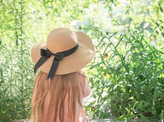 Little girl in a straw hat surrounded by  flowers. portrait of the happy little girl blonde with long hair. back view