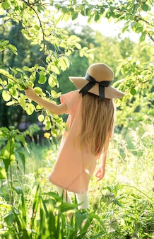 Little girl in a straw hat surrounded by  flowers