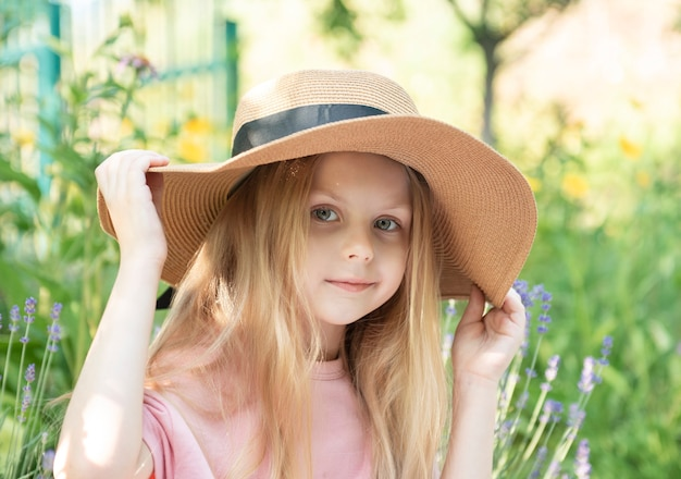Little girl in a straw hat surrounded by lavender flowers