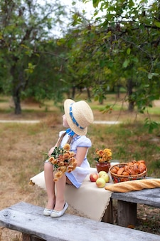 Little girl in straw hat with bouquet of flowers sits on bench on picnic in garden. summer vacation.