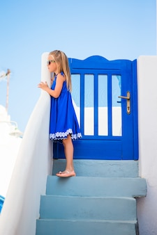 Little girl at street of typical greek village with white walls and steps in greece