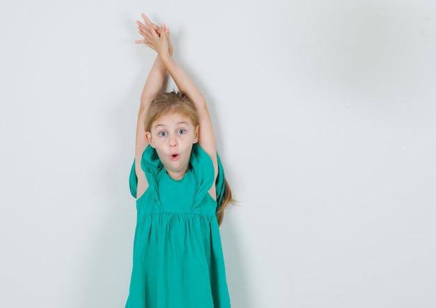 Bambina che allunga le braccia sopra la testa in abito verde e sembra sorpresa. vista frontale.