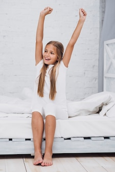 Little girl stretching in bedafter waking up