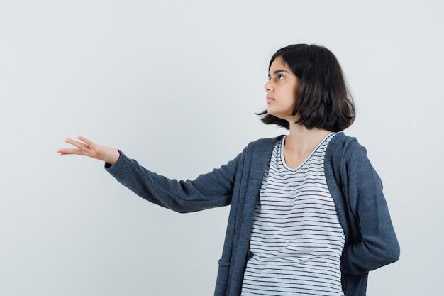 Маленькая девочка вопросительно протягивает руку в футболке, куртке и выглядит смущенной
