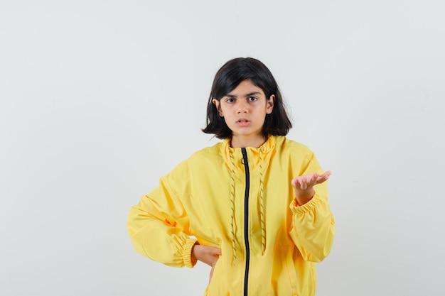 Bambina che allunga la mano in modo interrogativo in felpa con cappuccio gialla e sembra perplessa, vista frontale.