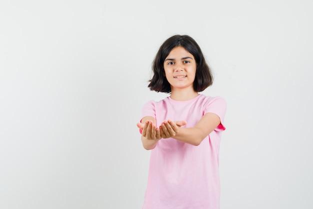 Маленькая девочка в розовой футболке протягивает сложенные ладони и выглядит весело. передний план.