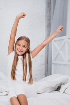 Little girl stretching while looking at the camera