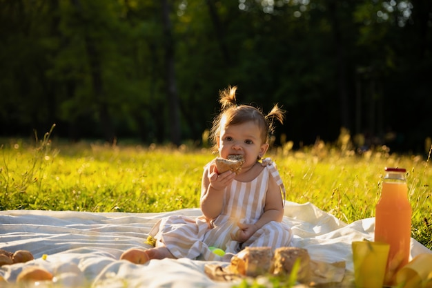 Little girl in a striped dress on a picnic in a city park.