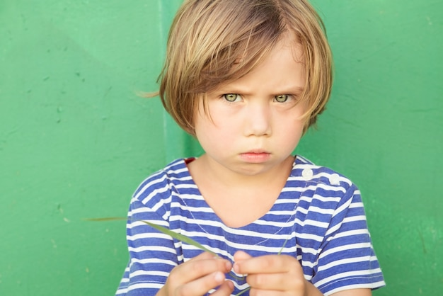 Little girl in a striped dress with  scowl on her face
