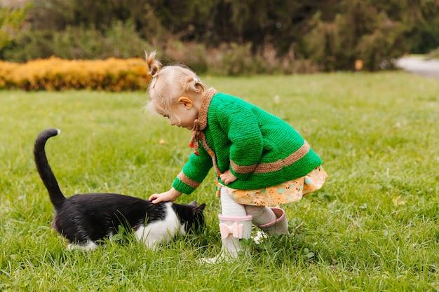 公園で黒猫をなでる少女。猫をなでる女の子。子供と動物。
