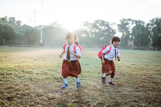 Little girl student running together while going to their school