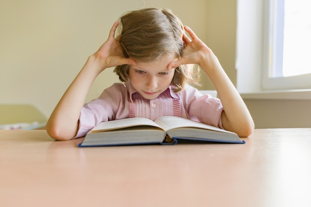 本を机で勉強して小さな女子学生。