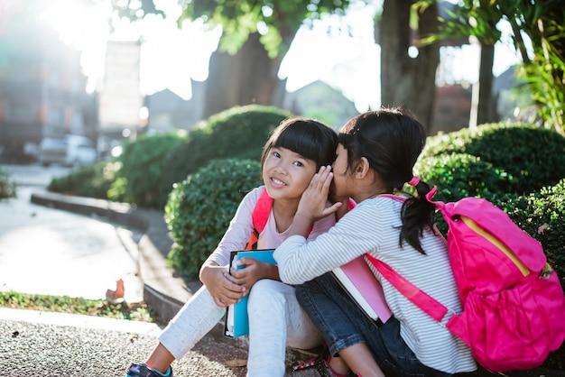 Little girl student whispering to her friend
