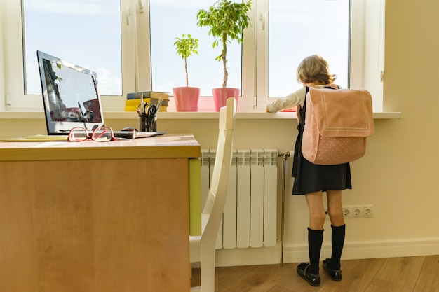 Little girl student with backpack in school uniform looks out the window