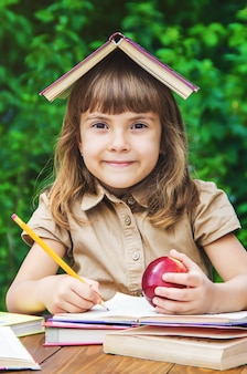 Little girl student with a red apple. selective focus. nature.